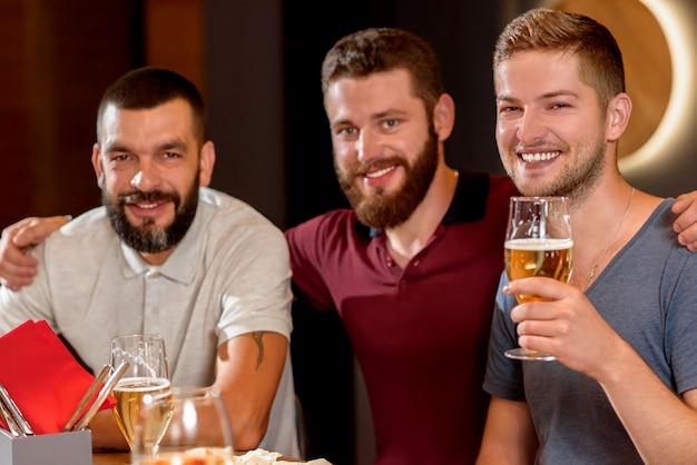 Tres hombres guapos sonriendo, mirando a cámara y sosteniendo un vaso de cerveza.