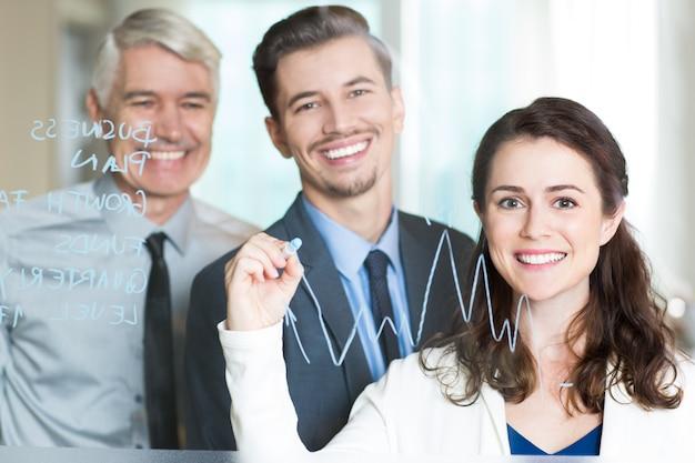 Tres hombres de negocios sonrientes que drenan el gráfico