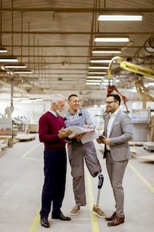 Tres hombres parados y discuten en fábrica de muebles.