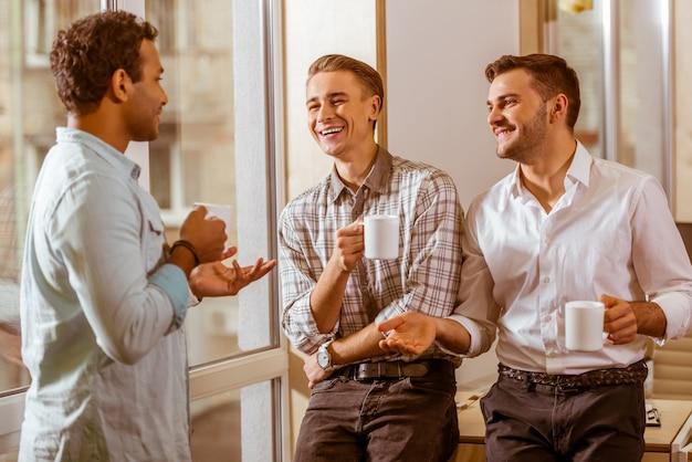 Tres hombres se paran en la oficina y discuten la idea de negocio.