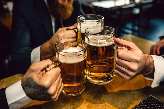 Tres hombres de traje mantienen juntas jarras de cerveza. se sientan a la mesa.