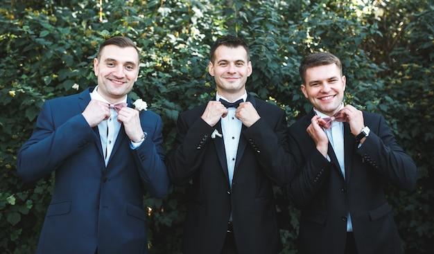 Tres, hombres, trajes, posar, jardín
