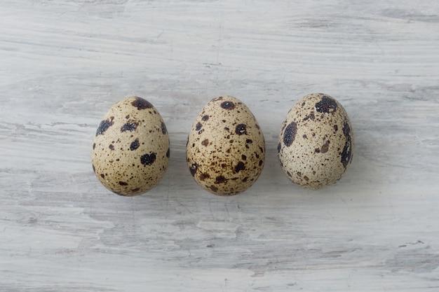 Tres huevos de codorniz sobre un fondo blanco vintage
