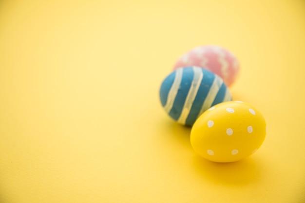 Tres huevos de pascua coloridos en mesa