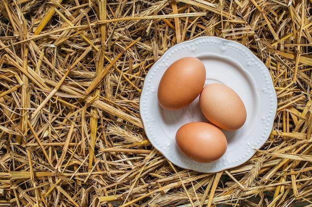 Tres huevos en un plato sobre paja
