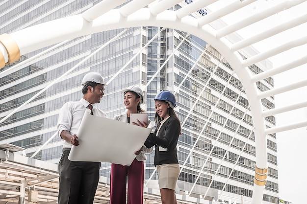 Tres ingenieros de construcción trabajando al aire libre en el sitio de construcción