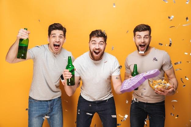 Tres jóvenes aficionados al fútbol entusiasmados celebrando