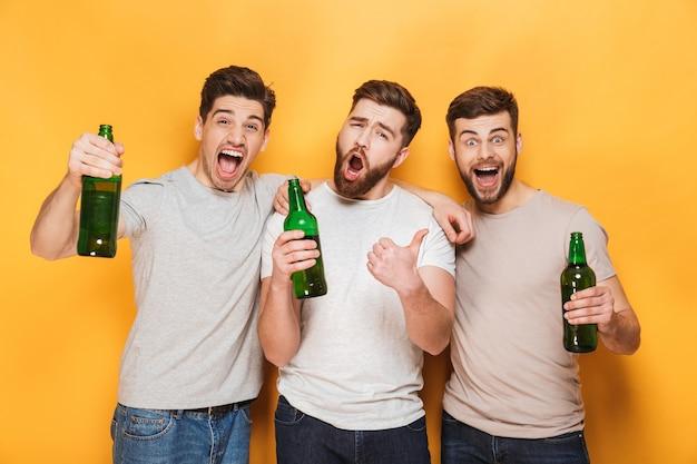 Tres jóvenes alegres sosteniendo cerveza y celebrando