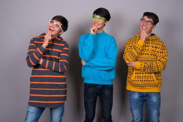 Tres jóvenes amigos asiáticos juntos contra la pared gris