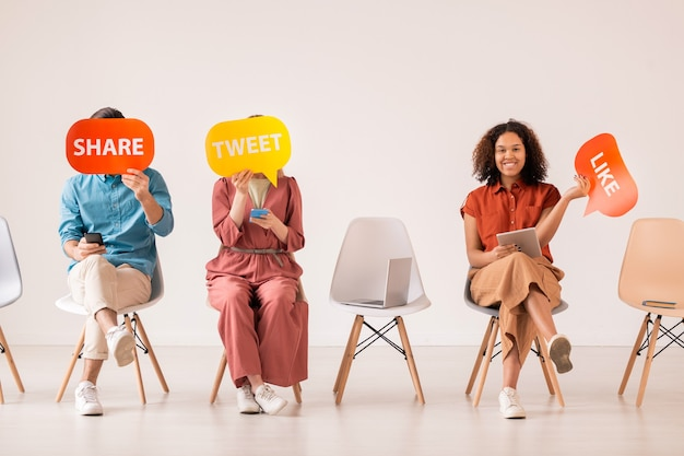 Tres jóvenes amigos casuales con dispositivos móviles que sostienen bocadillos de papel multicolor mientras se comunican en las redes sociales