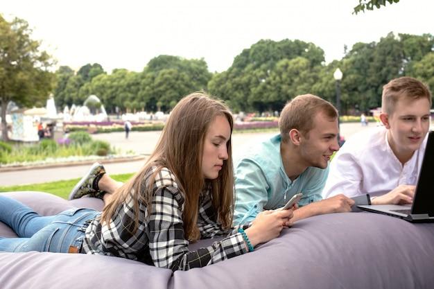 Tres jóvenes amigos relajarse al aire libre en el parque en un gran cojín.