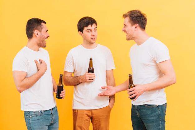 Tres jóvenes amigos varones disfrutando de la cerveza de pie contra el fondo amarillo