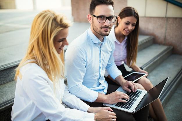 Tres jóvenes colegas alegres sonrientes trabajando juntos en la computadora portátil