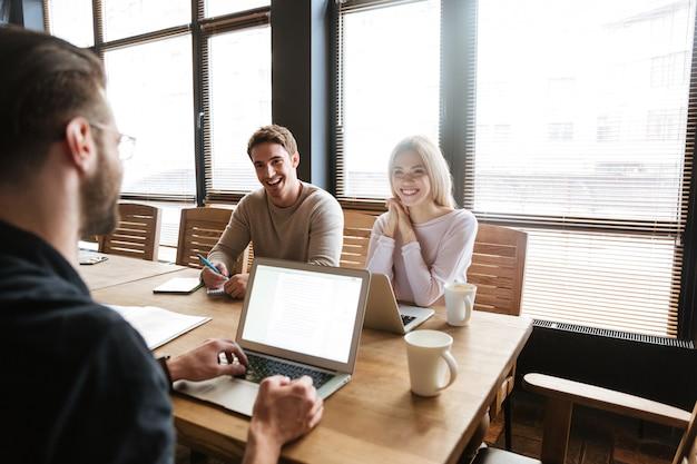 Tres jóvenes colegas alegres trabajan con computadoras portátiles