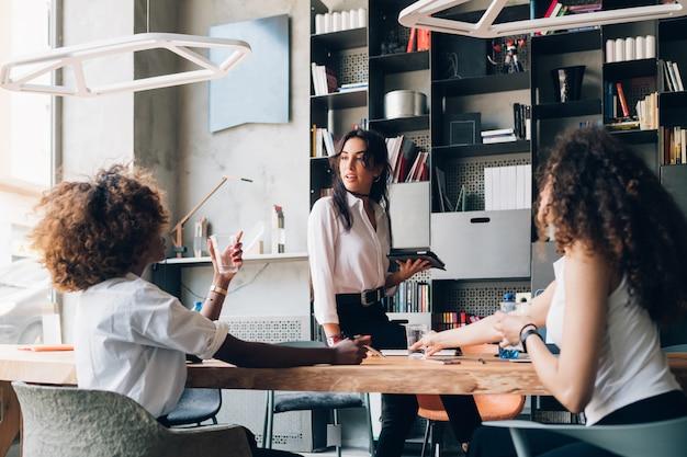 Tres jóvenes colegas multiculturales discutiendo un proyecto en una oficina moderna