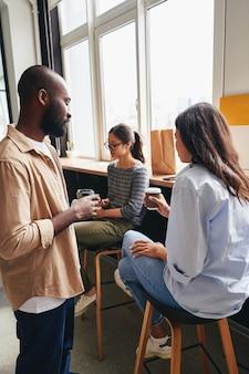 Tres jóvenes colegas tomando un café juntos