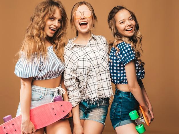 Tres jóvenes con estilo sexy sonrientes hermosas chicas con patinetas coloridas centavo. mujeres en ropa de camisa a cuadros de verano posando en gafas de sol. modelos positivos divirtiéndose