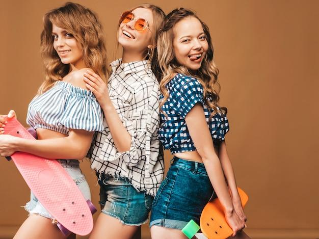 Tres jóvenes con estilo sonrientes hermosas chicas con patinetas coloridas centavo. mujer en ropa de camisa a cuadros de verano posando. modelos positivos divirtiéndose