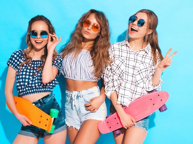 Tres jóvenes con estilo sonrientes hermosas chicas con patinetas coloridas centavo. mujeres en ropa de verano posando en gafas de sol. modelos positivos divirtiéndose