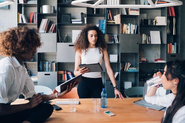 Tres jóvenes estudiantes multiculturales discutiendo proyecto en la oficina de coworking
