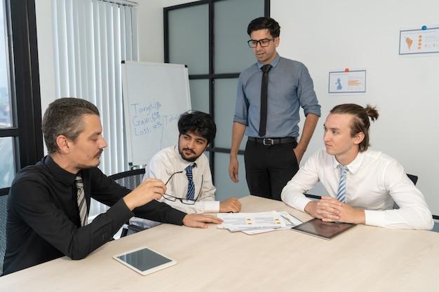 Tres jóvenes gerentes informando al jefe serio.