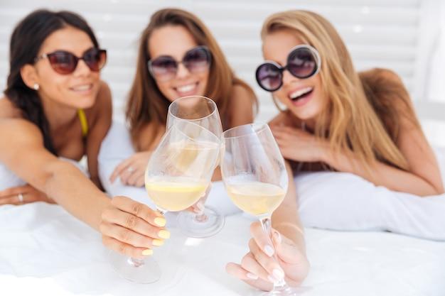 Tres jóvenes hermosas chicas felices en bikini bebiendo al aire libre