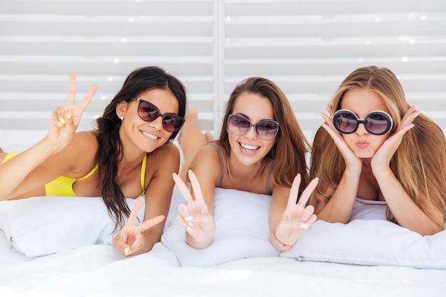 Tres jóvenes hermosas chicas felices en bikini bebiendo y mostrando el signo v al aire libre