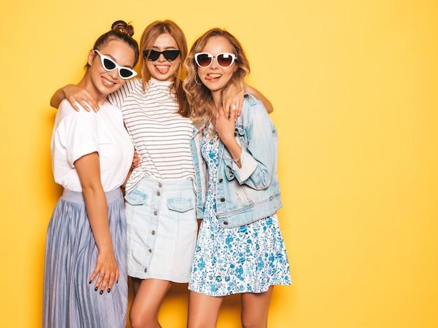 Tres jóvenes hermosas chicas hipster sonrientes en ropa de moda de verano. mujeres despreocupadas atractivas que presentan cerca de la pared amarilla. modelos positivos divirtiéndose en gafas de sol