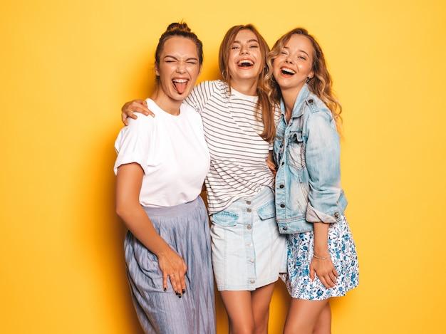 Tres jóvenes hermosas chicas hipster sonrientes en ropa de moda de verano. mujeres despreocupadas atractivas que presentan cerca de la pared amarilla. modelos positivos divirtiéndose mostrando lengua