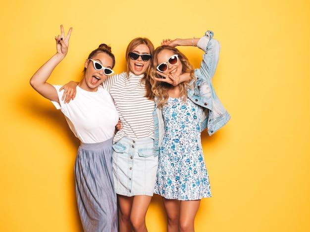 Tres jóvenes hermosas chicas hipster sonrientes en ropa de moda de verano. mujeres despreocupadas atractivas que presentan cerca de la pared amarilla. modelos positivos divirtiéndose. muestran el signo de la paz