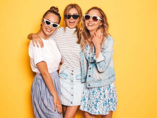 Tres jóvenes hermosas chicas hipster sonrientes en ropa de moda de verano. mujeres despreocupadas atractivas que presentan cerca de la pared amarilla. modelos positivos divirtiéndose
