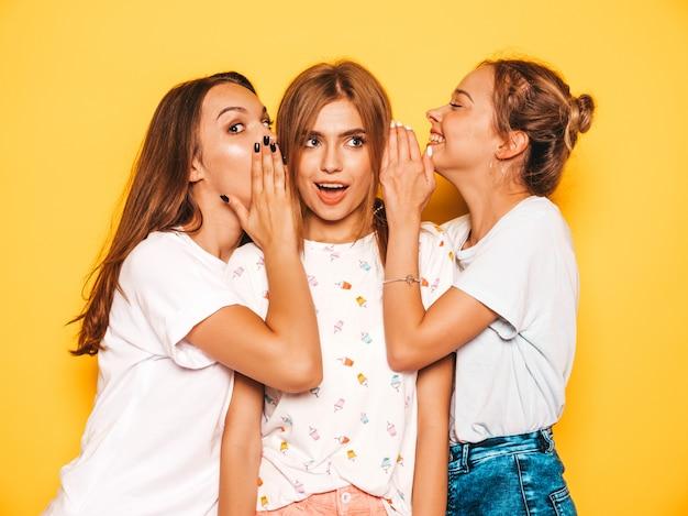 Tres jóvenes hermosas chicas hipster sonrientes en ropa de moda de verano. mujeres despreocupadas atractivas que presentan cerca de la pared amarilla. modelos positivos que se vuelven locos y se divierten. compartan secretos, chismes