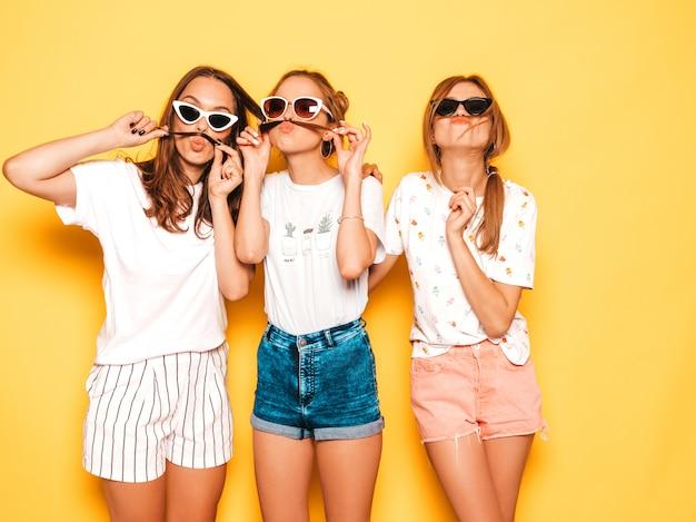 Tres jóvenes hermosas chicas hipster sonrientes en ropa de moda de verano. mujeres despreocupadas atractivas que presentan cerca de la pared amarilla. modelos positivos que se vuelven locos y se divierten. hacer bigote con pelo