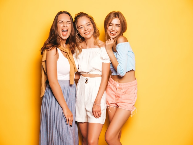 Tres jóvenes hermosas chicas hipster sonrientes en ropa de moda de verano. mujeres despreocupadas atractivas que presentan cerca de la pared amarilla. modelos positivos volviéndose locos y divirtiéndose. en gafas de sol