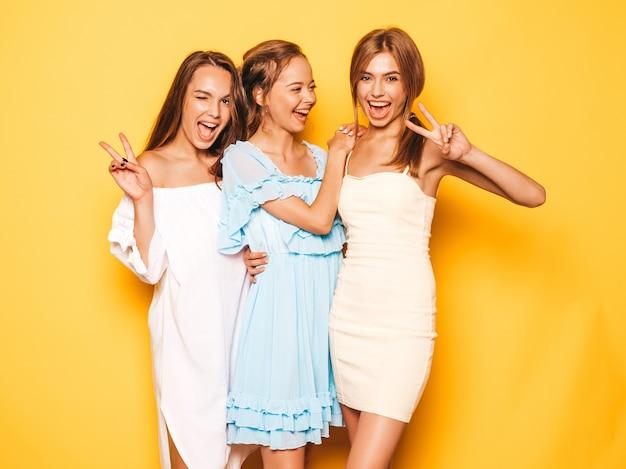 Tres jóvenes hermosas chicas hipster sonrientes en ropa de moda de verano. mujeres despreocupadas atractivas que presentan cerca de la pared amarilla. modelos positivos volviéndose locos y divirtiéndose. muestra el signo de la paz