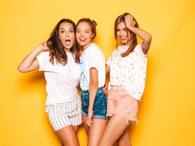 Tres jóvenes hermosas chicas hipster sonrientes en ropa de moda de verano. mujeres despreocupadas atractivas que presentan cerca de la pared amarilla. modelos positivos volviéndose locos y divirtiéndose.