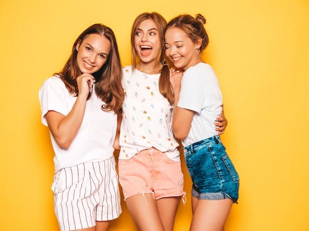 Tres jóvenes hermosas chicas hipster sonrientes en ropa de moda de verano. mujeres despreocupadas atractivas que presentan cerca de la pared amarilla. modelos positivos volviéndose locos y divirtiéndose