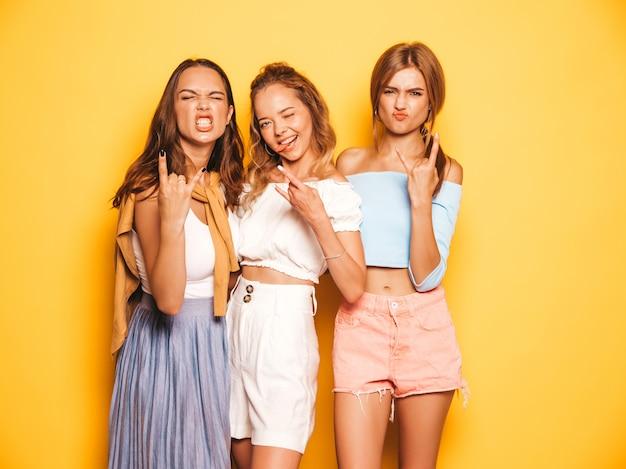 Tres jóvenes hermosas chicas hipster sonrientes en ropa de moda de verano. mujeres despreocupadas atractivas que presentan cerca de la pared amarilla. los modelos positivos se vuelven locos y se divierten. muestran signos de rock and roll