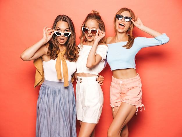 Tres jóvenes hermosas chicas hipster sonrientes en ropa de moda de verano. mujeres despreocupadas atractivas que presentan cerca de la pared rosada. modelos positivos divirtiéndose en gafas de sol