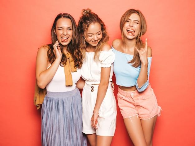 Tres jóvenes hermosas chicas hipster sonrientes en ropa de moda de verano. mujeres despreocupadas atractivas que presentan cerca de la pared rosada. modelos positivos divirtiéndose. muestran lengua
