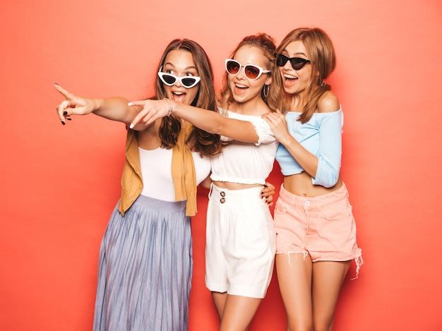 Tres jóvenes hermosas chicas hipster sonrientes en ropa de moda de verano. mujeres despreocupadas atractivas que presentan cerca de la pared rosada. modelos positivos divirtiéndose. señalando las ventas de la tienda.
