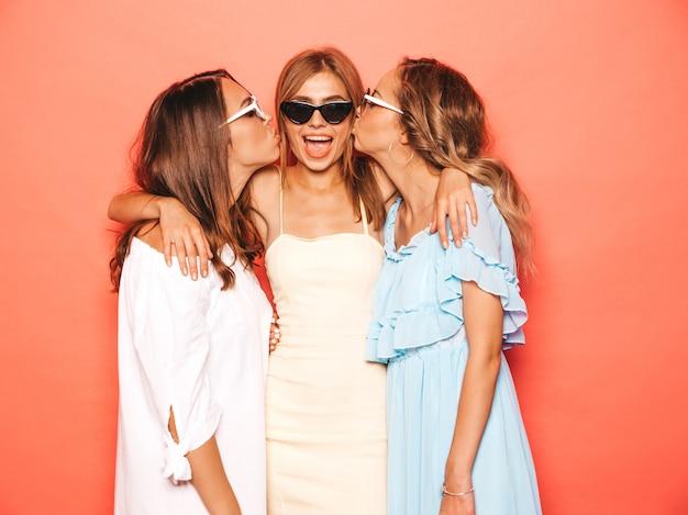 Tres jóvenes hermosas chicas hipster sonrientes en ropa de moda de verano. mujeres despreocupadas atractivas que presentan cerca de la pared rosada. modelos positivos volviéndose locos y divirtiéndose besando a su amigo en la mejilla