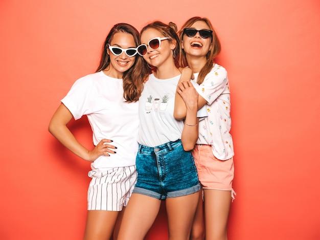 Tres jóvenes hermosas chicas hipster sonrientes en ropa de moda de verano. mujeres despreocupadas atractivas que presentan cerca de la pared rosada. modelos positivos volviéndose locos y divirtiéndose. en gafas de sol