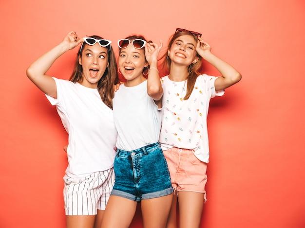 Tres jóvenes hermosas chicas hipster sonrientes en ropa de moda de verano. mujeres despreocupadas atractivas que presentan cerca de la pared rosada. modelos positivos volviéndose locos y divirtiéndose