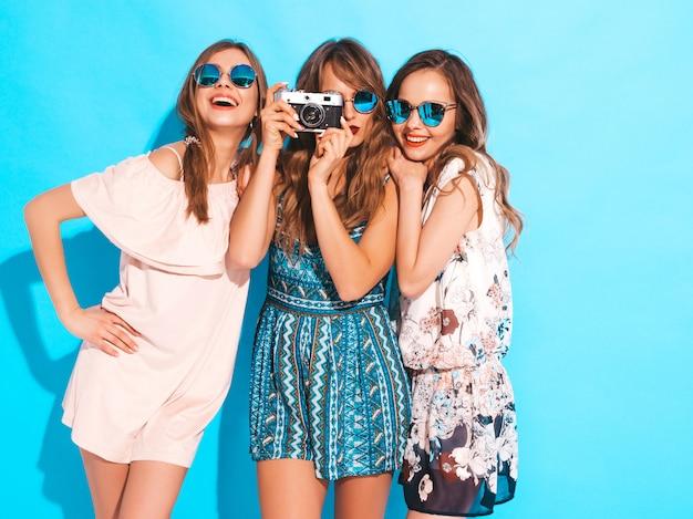 Tres jóvenes hermosas chicas sonrientes en moda verano coloridos vestidos y gafas de sol. sexy mujer despreocupada posando. tomar fotos en cámara retro