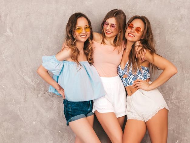 Tres jóvenes hermosas chicas sonrientes en ropa de moda de verano. sexy mujer despreocupada posando. modelos positivos divirtiéndose. abrazando