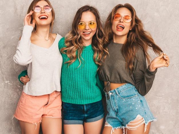 Tres jóvenes hermosas sonrientes hermosas chicas en ropa de moda de verano. sexy mujer despreocupada posando. modelos positivos divirtiéndose en gafas de sol redondas