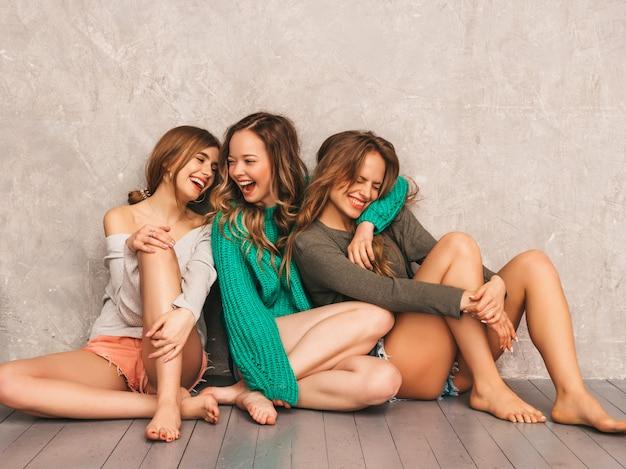 Tres jóvenes hermosas sonrientes hermosas chicas en ropa de moda de verano. sexy mujer despreocupada posando. modelos positivos divirtiéndose. sentado en el suelo