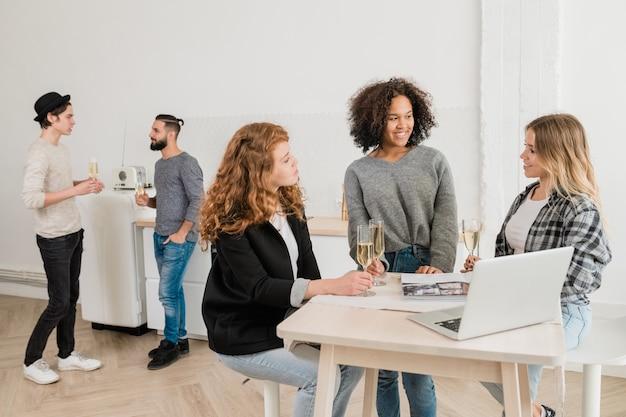 Tres jóvenes mujeres casuales con champán discutiendo algo por escritorio frente a la computadora portátil con dos chicos hablando