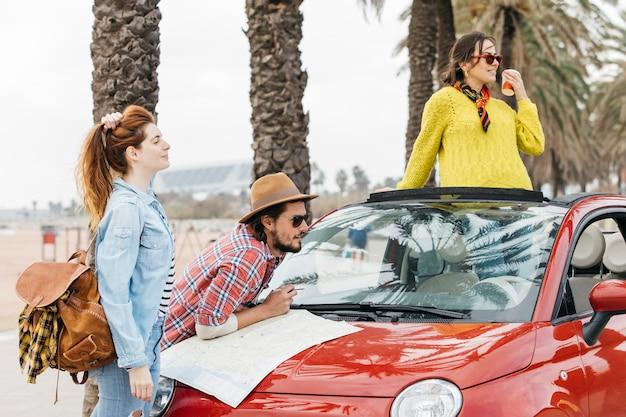 Tres jóvenes de pie cerca de un coche con un mapa de carreteras